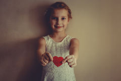 A girl with red heart in her hands. 