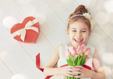 Girl with red heart. Sweet child girl with red heart and bouquet of tulips. Happy little girl with Valentine's gift lying on white wooden floor. Wedding Royalty Free Stock Image