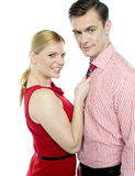 Girl in red holding businessman by his tie Royalty Free Stock Photography