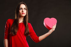 Girl in red holding heart box. Stock Image