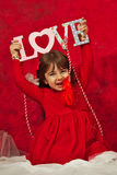 A girl in red holding a Love sign stock photo