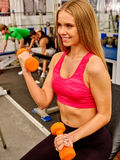 Girl in red holding orange dumbbells into sport gym. Royalty Free Stock Photo