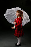 Girl in red holding a parasol. Girl in red outfit holding a white parasol Stock Photos