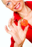 Girl in red holding strawberry slice Stock Photography