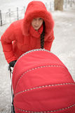 Girl in Red Hood. Winter Girl in Red Hood with Baby Carriage Outdoors Stock Image