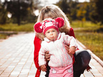 Girl in a red jacket and cap with mother Stock Photo