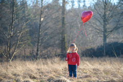Girl in a red jacket with heart-shaped balloon Royalty Free Stock Photo