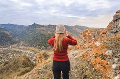 A girl in a red jacket looks out into the distance on a mountain, a view of the mountains and an autumnal forest by an overcast da Royalty Free Stock Photos