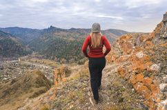 A girl in a red jacket looks out into the distance on a mountain, a view of the mountains and an autumnal forest by an overcast da Stock Photography