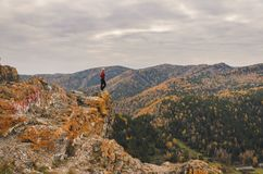A girl in a red jacket looks out into the distance on a mountain, a view of the mountains and an autumnal forest by an overcast da Stock Images
