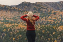 A girl in a red jacket looks out into the distance on a mountain, a view of the mountains and an autumnal forest by an overcast da Royalty Free Stock Images