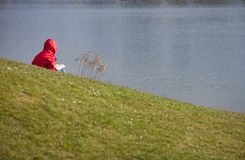 Girl in red jacket reading at lake side Royalty Free Stock Images