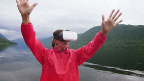 The girl in the red jacket is standing on the pier In virtual reality glasses stock video footage