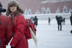 girl in a red jacket walking on Red Square in heavy snow Royalty Free Stock Photos