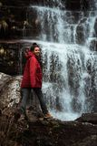 Girl in red jacket by the waterfall. Girl in red winter jacket by the waterfall hiking river cold travel nature forest serbia stara planina alone hiker outdoor royalty free stock photo