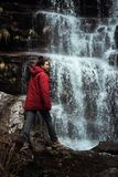 Girl in red jacket by the waterfall. Girl in red winter jacket by the waterfall hiking river cold travel nature forest serbia stara planina alone hiker outdoor royalty free stock photography