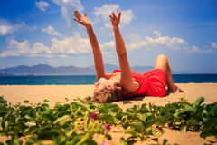 Girl in red lies on sand lifts hands near foreground creepers Stock Photo