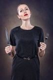 Girl with red lips. With a fork and knife royalty free stock photography