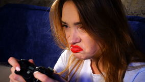 Girl with red lips holding a joystick and plays in a computer game stock video footage