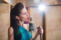 Girl with red lips holding a microphone and singing Royalty Free Stock Image