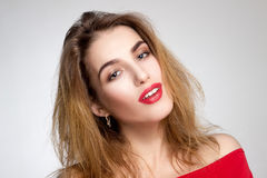 Girl with red lips looking at camera. Horizontal portrait of pretty young girl with red lips in studio looking at the camera Royalty Free Stock Image