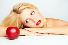 Girl with red lips and a red apple Royalty Free Stock Image