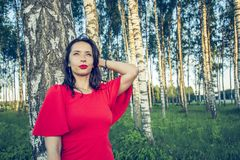 A girl with red lips in a red dress is standing in a birch grove dreaming holdin her hand near the head stock photo