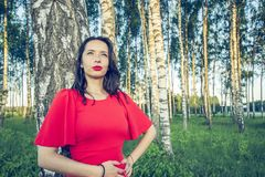 A pregnant woman with red lips in a red dress is standing in a birch grove and smile dreaming stock photo