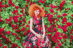 Girl with red lips in rose print dress on summer garden. Spring blossom flower. Redhead model in summer hat on valentines backgrou royalty free stock photography