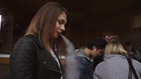 Girl with red lips smoke electronic cigarette on street. Vaper festival. Smile. In camera. Slow motion stock footage