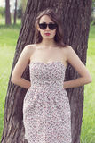 Girl with red lips in the sundress and in the sunglasses looks s Royalty Free Stock Images