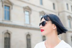 Girl with red lips in sunglasses pose on city street. Girl or woman with red lips in sunglasses pose on city street on sunny day. Fashion, beauty, look, style Stock Photo