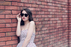 Girl with red lips in the sunglasses and in the sundress near th Stock Photo