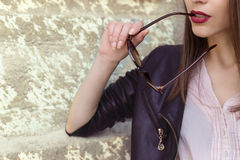 Girl with red lipstick in a black leather jacket sunglasses bit Stock Photo