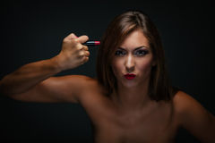 Girl With Red Lipstick. Portrait of a beautiful young woman holding lipstick as a weapon. Looking at camera and having fun Stock Photo