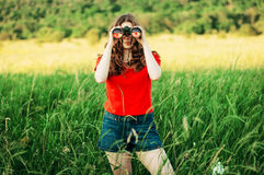 Girl in a red  looking through binoculars. woman looking through Stock Photo
