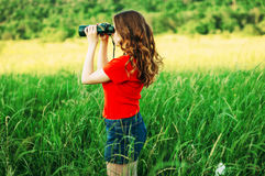 Girl in a red  looking through binoculars. woman looking through Royalty Free Stock Photos