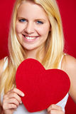 Girl with red love heart. Portrait of blond haired girl with red love heart shape Royalty Free Stock Image