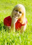 Girl in red lying on  grass Stock Photos