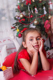 Girl in red lying under Christmas tree Stock Images