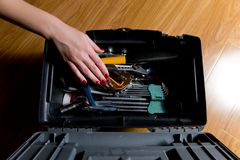 Girl with red manicure reaches for the tools in the tool box