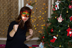 Girl in a red mask near a Christmas tree with sparkler. stock photo