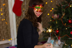 Girl in a red mask near a Christmas tree with sparkler. royalty free stock image
