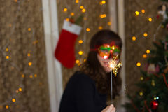 Girl in a red mask near a Christmas tree with sparkler. royalty free stock photo