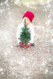 Girl In Red Mittens and Cap Holds Small Christmas Tree in Snow Stock Images