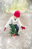 Girl In Red Mittens and Cap Near Small Christmas Tree with Snow Stock Photography