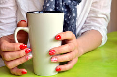 Girl with red nails on her fingers hold white cup, closeup Stock Image