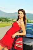 Girl in red near car. Attractive girl in red dress standing  near car Stock Photo