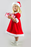 Girl in red new year cap with a celebratory gift Stock Image