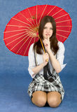 Girl with red oriental umbrella on blue Stock Photography